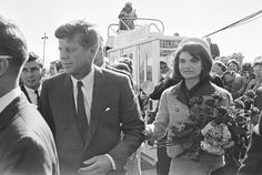 Mrs. Kennedy holds her husband's arm at Love Field. There was a time in American History when public displays of affection were uncommon. 1963 was part of that time.