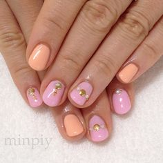 Uñas de color rosa con adornos dorados y naranja.