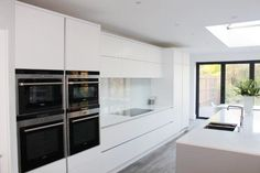 Matt white handleless kitchen. This bespoke kitchen is from the bespoke range at Kitchen & Bedroom Store. Matt white kitchen cabinets. Contact us for a quotation.