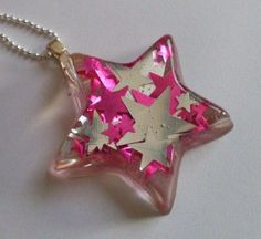 Star resin pendant with pink and silver stars embedded. #resin #stars #jewellery…