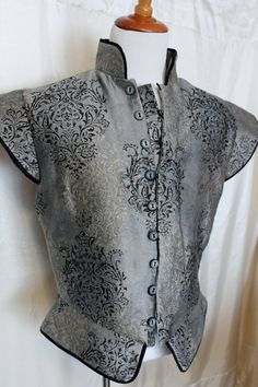 Gorgeous and lord worthy doublet! This fabric is fantastic! It is a silver grey with black and beige scroll pattern over top. Fully lined, and