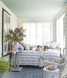 On this Maine cottage's porch, dogs Minnie (left) and Nash get cozy on an iron-and-brass ­daybed, sporting a vintage seersucker coverlet. The ­Moroccan rug is from Canvas.   - HouseBeautiful.com