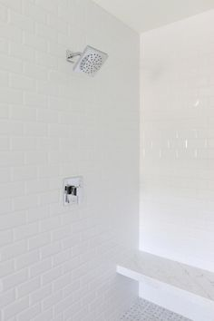 Sleek white master bath shower features white beveled subway tile surround fitted with a Moen 90 ...
