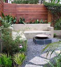 Cement corner sitting area with planters, fire place and stones