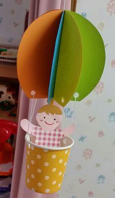 カラフルなドット柄の紙コップ(オレンジ・赤・水色)の気球に子どもが乗っています。全部で12個作りました。少しの風で気球がクルクル回りますよ(^^)小さめな紙コップも子ども達の服に使っている折り紙も100均で購入。15/4/6気球のモビール小