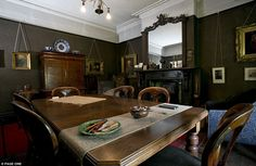 The dining room has dark painted walls, gilt-framed oil paintings hanging from a picture rail, and working fireplace