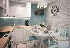 Love this little kitchen: the white cabinets, the turquoise wall, the corner bench and round table