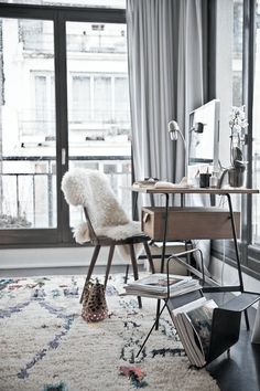 Wooden and black desk in bedroom with plush rug, magazine rack, gray draperies, beautiful view, orchid plant on desk.