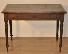 A lovely rustic Victorian mahogany writing table. We date this table to the late 19th century. The table sits on four long slender downward tapered turned legs. The main table is fitted with a central long drawer flanked by a pair of smaller drawers. The drawers are fitted with bakelite handles, the handles are not original and have been replaced at some point in the past. Some of the drawers have later added internal wood bars to break them into compartments. The table surface has a dark…