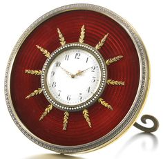 A Fabergé silver-gilt and enamel timepiece, workmaster Michael Perchin, St Petersburg, 1895-1899. Circular, the surface enamelled in translucent strawberry red over concentric wavy engine-turning, the seed pearl bezel within radiating gold oak leaf sprays, chased leaf tip border, silver scroll strut. Provenance: Possibly purchased by the current owner's mother from Wartski in the 1930s, or acquired from her friend, Grand Duchess Xenia Alexandrovna.