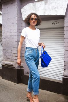 This blue purse adds the perfect touch of color to this look.
