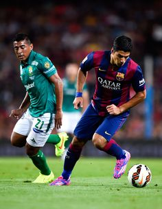 Luis Suarez of FC Barcelona competes for the ball with Luis Delgado of Club Leon during the Joan Gamper Trophy match between FC Barcelona and Club Leon at Camp Nou on August 18, 2014 in Barcelona, Catalonia.