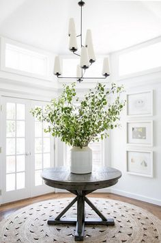 Modern Farmhouse Foyer Features Round Driftwood Table And Chandelier From Circa Lighting Chango