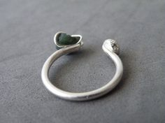 This gorgeous raw Emerald adjustable ring is a great piece for your everyday wear. The Emerald is firmly held by sterling silver prongs on one side, and on the other side is a lovely organic sterling nugget. Fantastic gift idea for someone special, this dual gemstone ring is simple, yet stylish.  ***Please refer to the Official International Ring Size Conversion Chart, to determine your measure: http://www.ringsizes.co/   This ring is also available with: Raw Onyx…