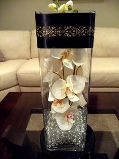 "Diy 16""Tall vase filled with beads and orchids wrapped with black laser cut ribbon at mouth of vase"