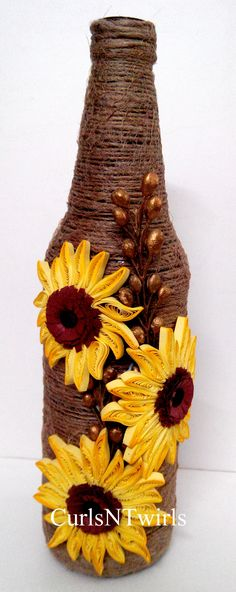 A beer bottle  wrapped up in brown jute rope and with quilled sunflowers in yellow around it .