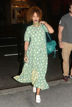While painting the town red in the city, RiRi delivered flower-meets-grunge '90s realness. While piling her kinky auburn tendrils on her head, she wore deep purple lipstick, a Versace-emblazoned choker, floral babydoll dress, and white sneakers.