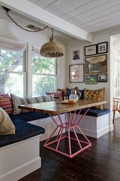 breakfast nook. love the patterned pillows & table, plus surrounding windows