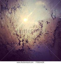 Beautiful frosty pattern on the window with sunlight