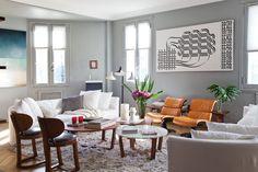 En el living, dos amplios sofás curvos contienen a las mesas 'Garupá' con tapa de mármol y de madera (Mesopotamia) sobre la alfombra de pelo largo (Gris Dimensión). Un dúo de sillones de los 60 en color suela y otro de sillitas de madera.  /Magalí Saberian