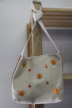 Another simple but beautiful design at Siyazenzela. This bag has orange button detailing and a colorful back, great bag for summer!