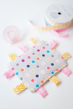 Taggie Baby Toy – a simple sewing project perfect for any new baby.  Colorful ribbons and a bright pattern makes this a great sensory toy for your little one.