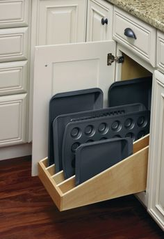 Diamond Cabinetry's roll out tray divider provides organized and easily accessible storage for baking sheets, trays, and more.
