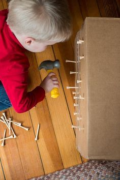 Pounding tees into a cardboard box - great idea for fine motor skills for toddlers!