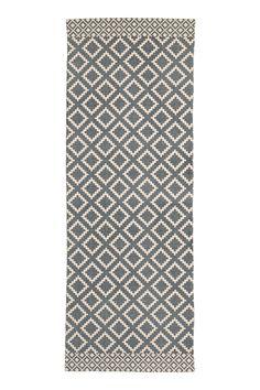 Alfombra rectangular en tejido de algodón con estampado en el lado superior.