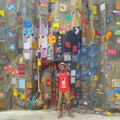 A fan in front of an installation by Ibrahim Mahama, the young Ghanaian artist creating radical public artworks from an everyday material - old jute cloth sacks. Many of these bags were initially used to transport cocoa. They are covered in markings that tell the story of what they once contained and where they've been. Chale Wote festival, Accra, Ghana – August 2014.