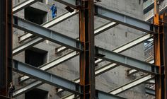 A worker walks on a steel girder at a building under construction in Nanjing, Jiangsu province, on May 5, 2011.