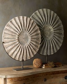 Disc-shaped sculptures are handcrafted of antiqued mango wood and are charmingly displayed on iron stands