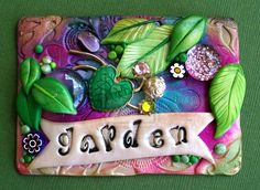 """Spring Garden ACEO.  The artist says:  """"I tried using alcohol inks on polymer clay...I had no idea what I was doing LOL!  The base of the ACEO is pearl white and I added drops of alcohol ink in a few colors and let them blend together.  Then I added handmade leaves with a pretty pearlized green.  Also included is an old jewelry pin, glass gems and a catseye cabochon.""""  . . . .   As with all ACEO, this measures 2.5"""" x 3.5""""."""