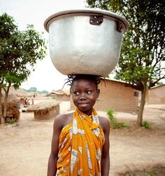 A young girl in Central African Republic carries water to her home. Photo by Scott Harrison.