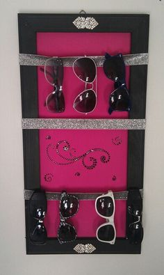 Made for my daughter's sunglasses.  Used back side of art canvas.  Painted hot pink,frame in black to match her room.  Silver ribbon hot glued to frame, sticker decals from Hobby Lobby.  And last but not least, some old pins found at a tag sale for a touch of bling.
