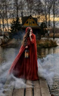 Fantasy - -Ilusion-fantasia: Fantasy - - Woman In Red Cloak in Forest by Dave and Les Jacobs for Stocksy United Red riding hood and the wolf Photo