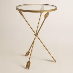 Distressed gold arrows create the tripod base of our side table, a unique accent next to your favorite chair or sofa. Topped with a glass surface, it's equally contemporary and charming.