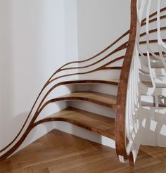 Creative wooden staircase designed by Atmos Studio for nature inspired residential house in London, England. The staircase was formed from a series of tree branch inspired threads that hang from above and merge into unique handrail.