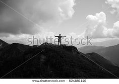 Man with open arms on the top of the mountain.