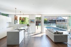 An open plan kitchen, living and dining effortlessly flows out onto a rear deck through a bank of floor-to-ceiling glass.