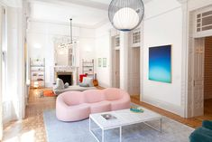 """The playful, modernist décor of the living room, seen here and throughout, is by Reunion Goods & Services; it includes Pierre Paulin's """"Pumpkin Sofa"""" from Ligne Roset, in all its lush pink plumpness, and at the far end of the room, the Prado daybed from Ligne Roset, which has detachable end cushions so the kids can take them off and put them on the floor to play."""