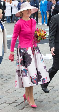 Queen Maxima dazzled in a fuscia pink top and cardigan worn over a floral A-line skirt from Dutch designer Natan, a firm favourite with European royals. She paired the look with a matching clutch and a broad-rimmed straw hat - finished off with some pink leather gloves and pointed courts.