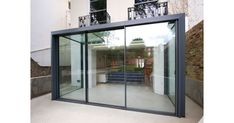 The versatile glass extension on this traditional home uses a glass roof & frameless structural glass sides which connect to our minimally framed sliding doors. Modern Conservatory, Glass Conservatory, Modern Patio Doors, Modern Exterior, Sliding Glass Door, Sliding Doors, Sliding Door Window Treatments, Glass Extension, Extension Ideas