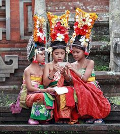 Reading a letter. Balinese teen girls wearing traditional outfit.