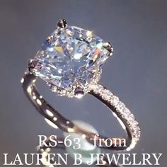 """## RS-63 from Lauren B Jewelry . Cushion cut centre stone with a micropave diamond incrusted setting on a 18K white gold band. Customize it by asking for a low profile and have the band be """"stackable"""". Straight band, no divets."""