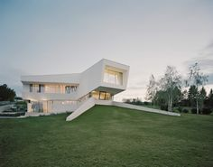 A white, sculpturally designed building structure stands confidently, seemingly untouchable, on a meadow surrounded with trees. On closer inspection, the qualities of this family home – delicately intertwined with the landscape and in no way imposing itself on its natural surroundings – become instantly apparent. The indoor and outdoor spaces transition into one another in perfect harmony.  Architecture: project A.01 architects Photography: Brigida Gonzalez Basement Color Schemes, Basement Colors, Building Structure, Building Design, Villas, Casa Clean, Concrete Fireplace, Tower House, Architecture Portfolio