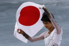Hanyu carries the Japanese flag after the flower ceremony during the Figure Skating Men's Free Skating Program at the Sochi 2014 Winter Olym...