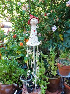 Eine hübsche Elfe als Windspiel für Ihren Garten. Die Figur wurde liebevoll teilglasiert und ist frostfest gebrannt. Am Saum ihres Kleides sind 8 Stränge mit Keramikkugeln angebracht. Die Figur...