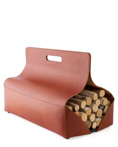 """The Allen log carrier, designed by Cristiana Giopato and Christopher Coombes for Frag, adds a dose of equestrian chic to the hearth. The 27"""" l. x 15"""" w. x 17"""" h. leather carrier has a wood base and flaps that close with hidden magnets. It costs $495 at Design Within Reach. 800-944-2233; dwr.com"""