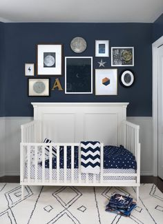 Nice blue nursery decor for boy. I love the art collection on the wall with the different size frames.
